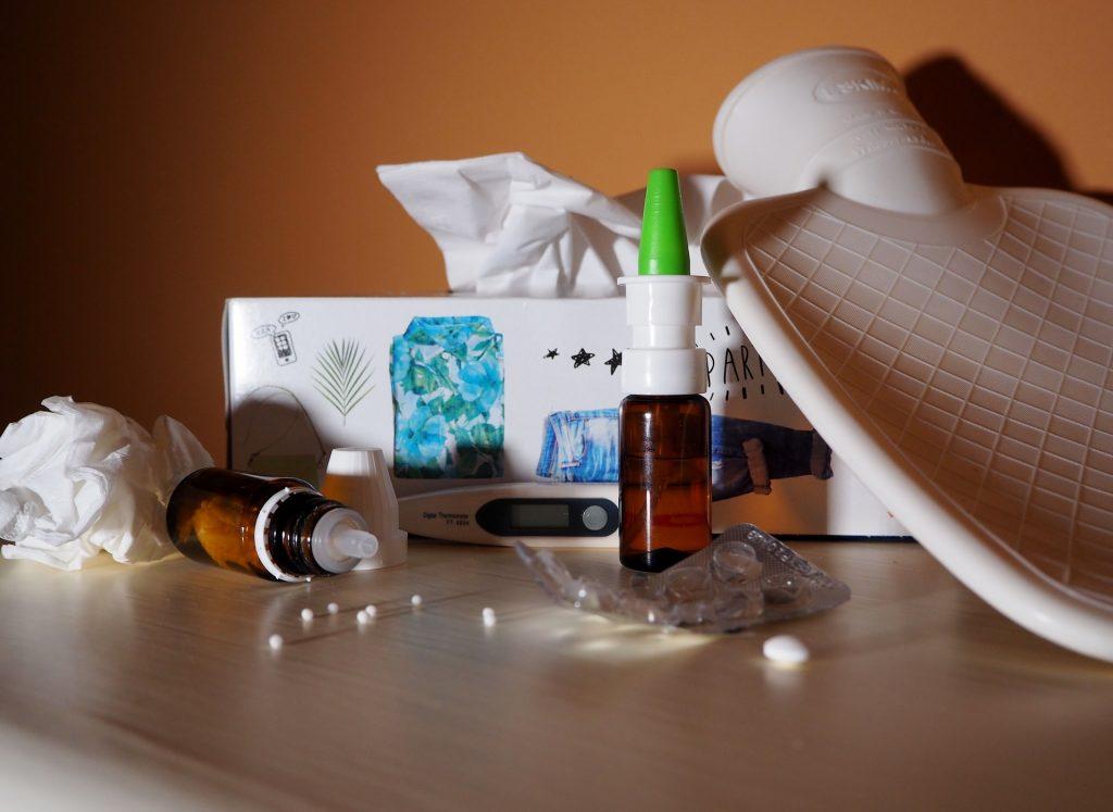 Eine Box mit Taschentüchern, Flasche Nasenspray, Fiebermesser, Wärmflasche und Medikamente