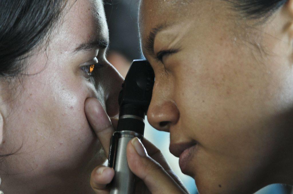 Eine Frau au schaut einer anderen Frau mit eine Lupe ins Auge